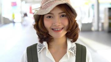 jovem atraente sorridente mulher asiática retrato ao ar livre na série de pessoas reais da cidade. video