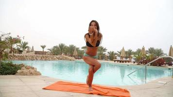 Beautiful positive woman sit at the swimming pool on the orange towel and meditating in yoga pose