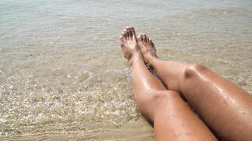 vrouwelijke voeten tegen de zee op het zomerstrand, tijd om te reizen. lege plek voor een tekst