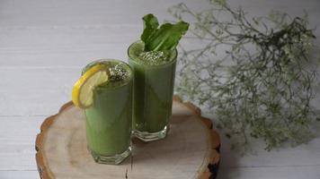 frullato verde miscelato con ingredienti o cocktail su sfondo bianco.