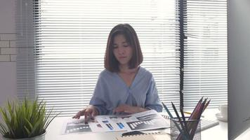 Asian business woman coming in her home office. video