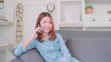 Young smiling Asian woman talking on smart phone with friends. video