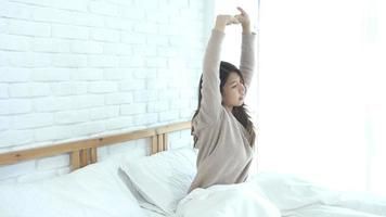 Happy beautiful young Asian woman waking up in morning. video