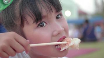 niña comiendo sushi japonés con palillos. video