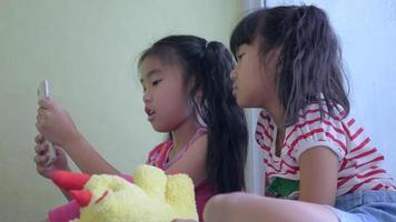Little girls using smart phone at home.	 video