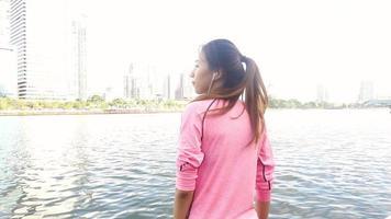 cámara lenta - mujer hermosa asiática en trajes de fitness está usando un reloj inteligente para escuchar música. video