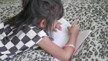 fille asiatique choisissant un crayon et faisant la maison dans le salon.