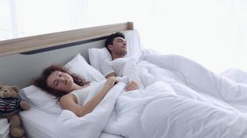casal acorda e se abraça na cama. video
