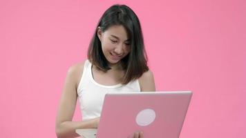 joven asiática que viene en la computadora portátil que controla las redes sociales en ropa casual y que mira la computadora.