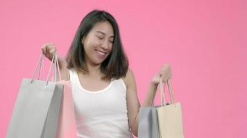 Young beautiful fashionable Asian woman holding shopping bags feeling happy smiling in casual clothing.