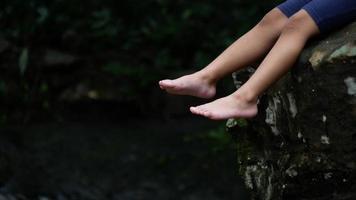 Nahaufnahme von entspannenden Beinen, die in der Natur baumeln.