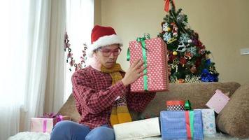 beau jeune homme ouvrant son cadeau de noël
