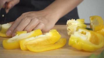 Frau hackt Paprika auf Schneidebrett