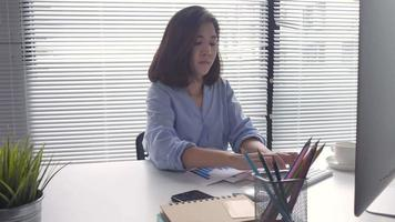 Young Asian woman coming on a computer