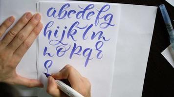 Frauenhand schreibt ein kalligraphisches Alphabet
