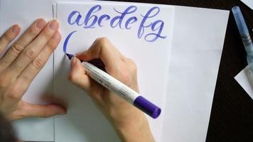 la mano della donna scrive un alfabeto calligrafico
