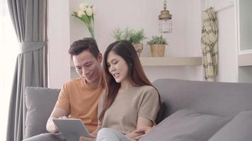 Asian couple using a tablet for online shopping