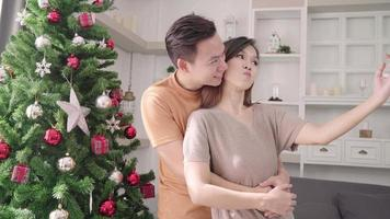 couple asiatique prenant selfies avec arbre de noël video