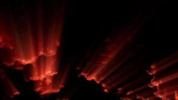 Rayas de luz roja dramáticas a través de las nubes en un espeluznante cielo negro