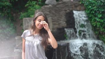junge Frau, die mit einem Wasserfall als Hintergrund aufwirft.