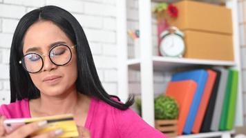 mulher digitando o número de um cartão de crédito em um telefone
