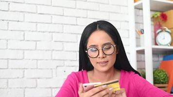mulher digitando o número de um cartão de crédito em um telefone video