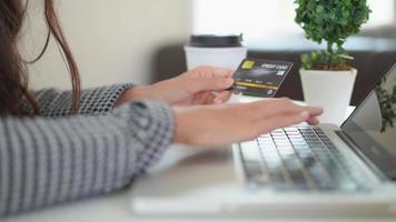jovem usando um cartão de crédito e um laptop para fazer compras online video