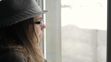 jovem olhando pela janela
