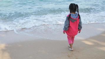 menina asiática brincando na praia