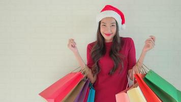 mulher com chapéu de Papai Noel e sacolas de compras video