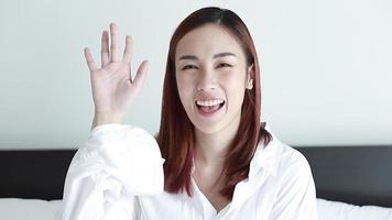 mujer vestida con camisa blanca diciendo adiós