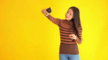 Woman taking selfies with her mobile phone on a yellow background