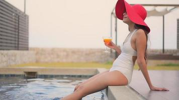 jovem mulher asiática relaxando na piscina