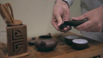 manos preparando té pu'er para la ceremonia del té video