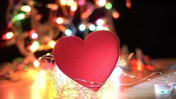 corazón de tela roja con luces centelleantes detrás
