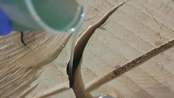 el leñador llena una grieta redonda en la madera con resina