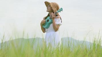 giovane donna che suona l'ukulele con sfondo di montagna