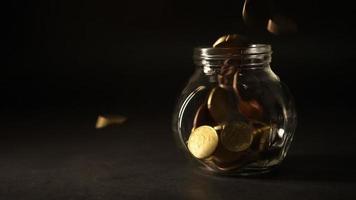 monedas de euro cayendo en un frasco de vidrio