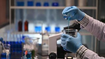 le mani di uno scienziato che mescola sostanze chimiche in un laboratorio
