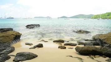 Playa rocosa con agua clara bajo un cielo azul nublado