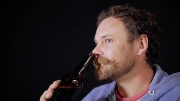 homem bebendo cerveja escura de uma garrafa