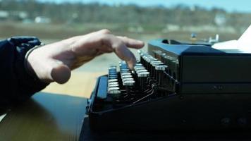 hombre escribiendo en una vieja máquina de escribir