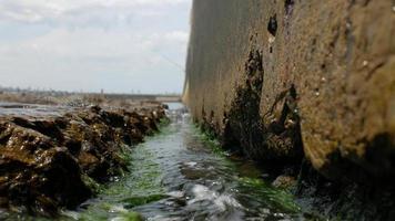 Olas del mar en las piedras y el muelle de hormigón.