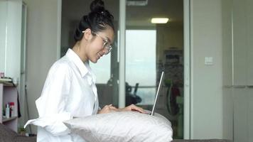 Beautiful Asian woman sitting on bed and coming on laptop
