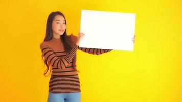 Woman with blank paper board on yellow background video
