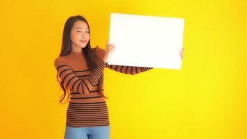 mulher com quadro de papel em branco sobre fundo amarelo