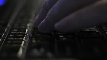 programador usando el teclado de una computadora portátil por la noche