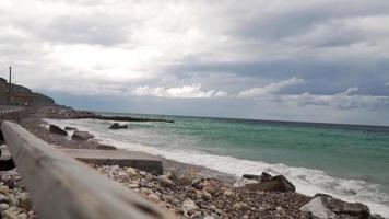 Pequeñas olas golpeando una playa rocosa en un día nublado