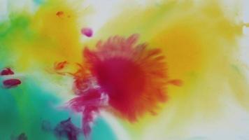tintas líquidas de acuarela en rosa cayendo sobre amarillo y azul