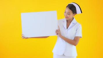 Thaise verpleegster met wit leeg bord